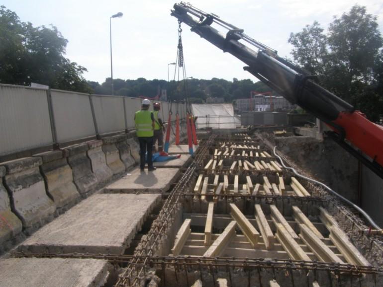 Les anciennes dalles de béton, datant de 1938, étaient dans un état très dégradé. Après avoir été découpées, elles sont enlevées une à une. On voit apparaître en-dessous la structure provisoire qui a été mise en place en 2012 pour soutenir la rampe d'accès au pont.