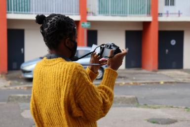 Une personne dans la rue qui tient un appareil photo et caméra