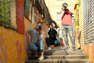 Trois personnes jeunes dans la rue assis sur des escaliers, en train de prendre des photos