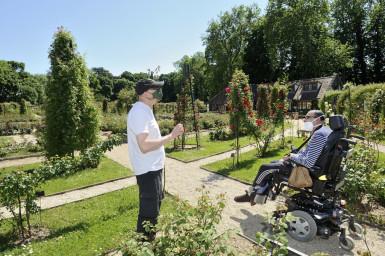 Une personne en fauteuil roulant se promène dans le parc de la roseraie du Val-de-Marne