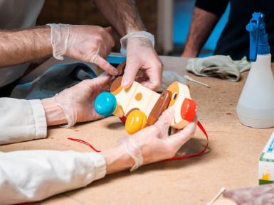 mains tenant un jouet à réparer