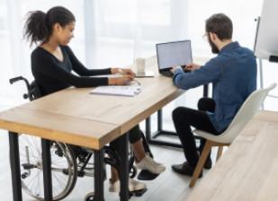 Femme en fauteuil roulant dans un bureau face à un homme valide