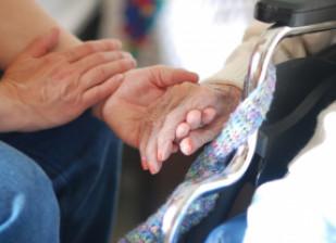 Aidant tenant la main d'une personne âgée