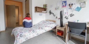 jeune assis sur son lit dans un foyer départemental