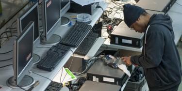 Un ouvrier travaille au reconditionnement d'un ordinateur.