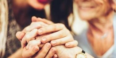 Aidant tenant la main d'une personne