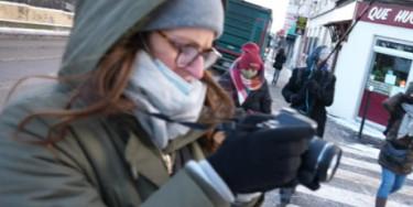 Une salariée tenant un appareil photo avec caméra dans les mains, pendant un tournage vidéo en extérieur