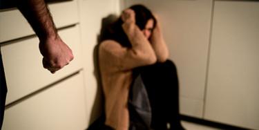 femme battue recroquevillée dans un coin